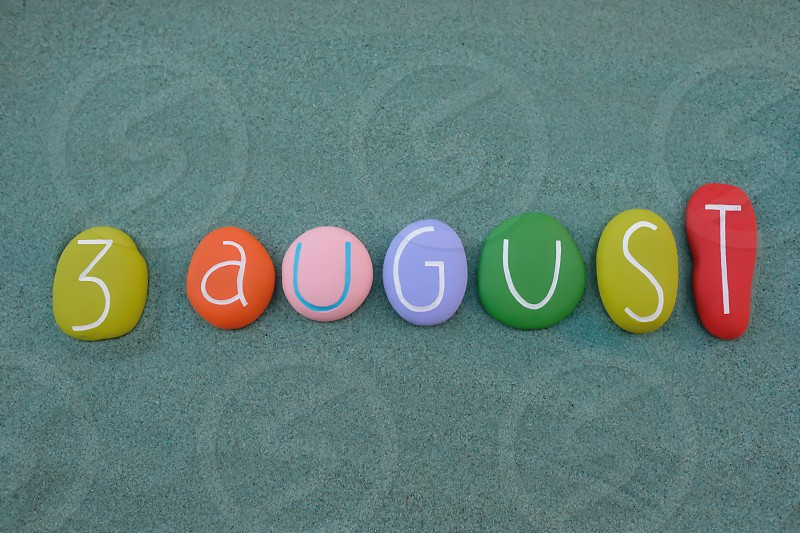 3 August calendar date composed with multi colored stones design over green sand photo