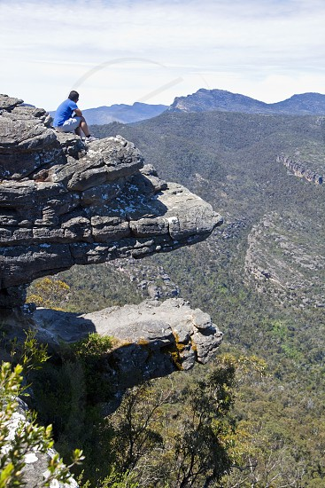 A man takes in the awesome view of The Grampians from a rocky outcrop known as the Balconies in Victoria Australia. photo