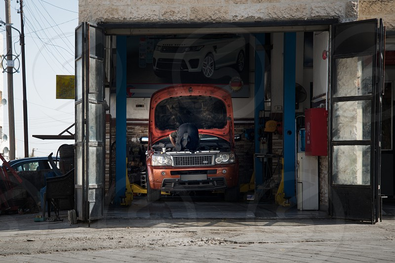 Man fixing cars in his shop in the industrial area photo