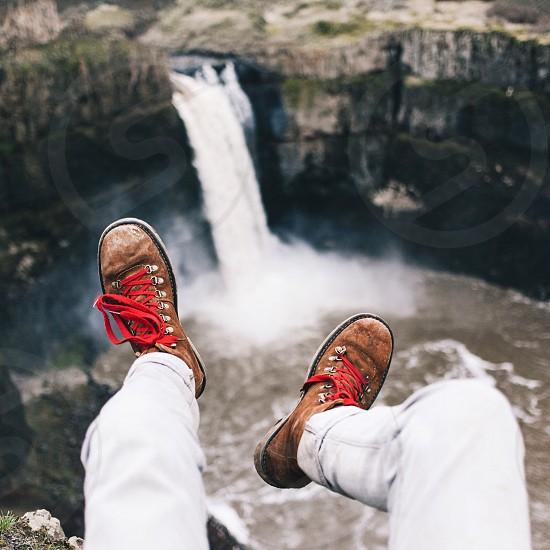 person in white denim pants sitting on mountain edge photo