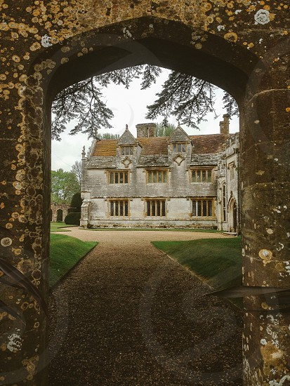 The world beyond the wall through the gateway stone arch kitchen English country garden stately home stone mullions trees nature driveway photo