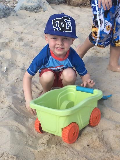 boy holding green toy wagon on sand photo