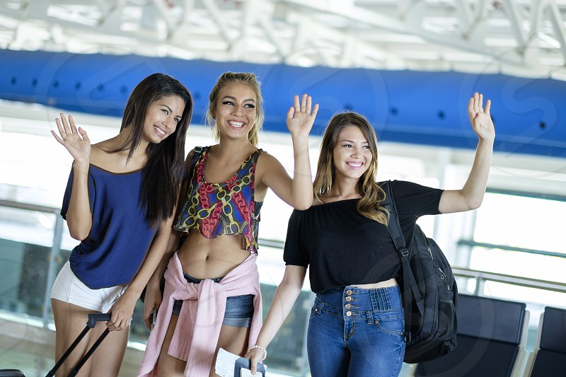 3 female teenager with luggage waving goodbye at airport terminal photo