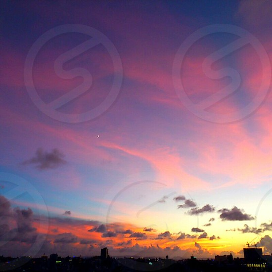 orange sunset over city under blue sky with grey clouds photo