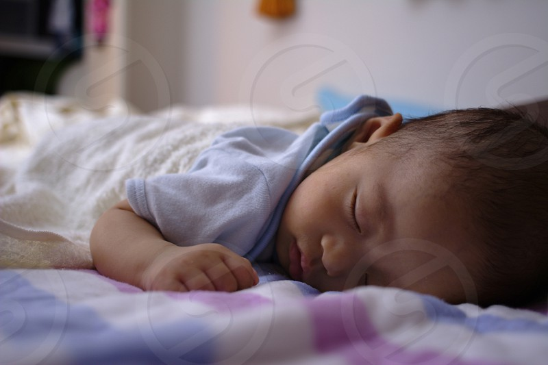 baby in blue short sleeve onesie sleeping on bed wrapped with white blanket photo