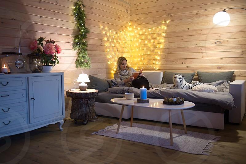 Woman read a book in cozy mountain cabin photo