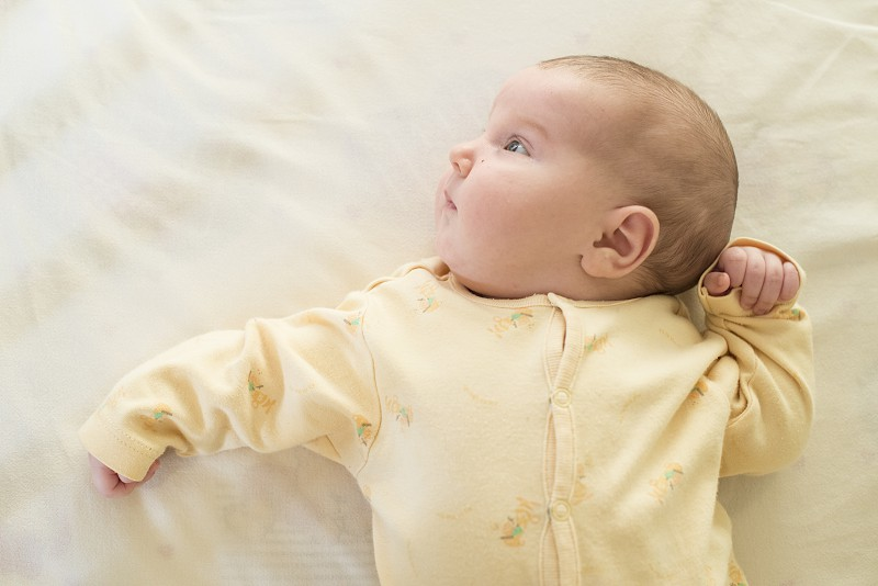 Baby in a baby bed. White clothes. Window light photo