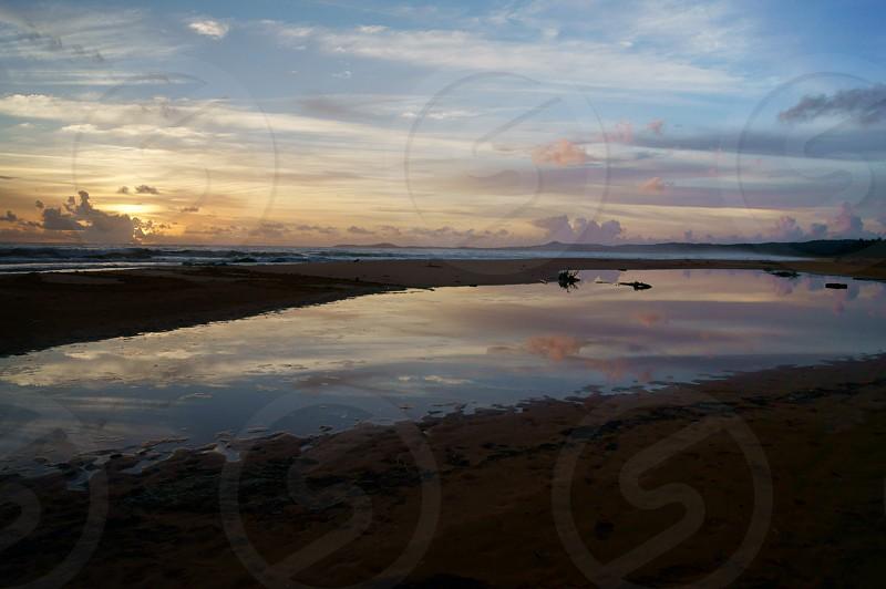 Sunrise at a isolated beach.  sun beach sky sand pond reflection  photo