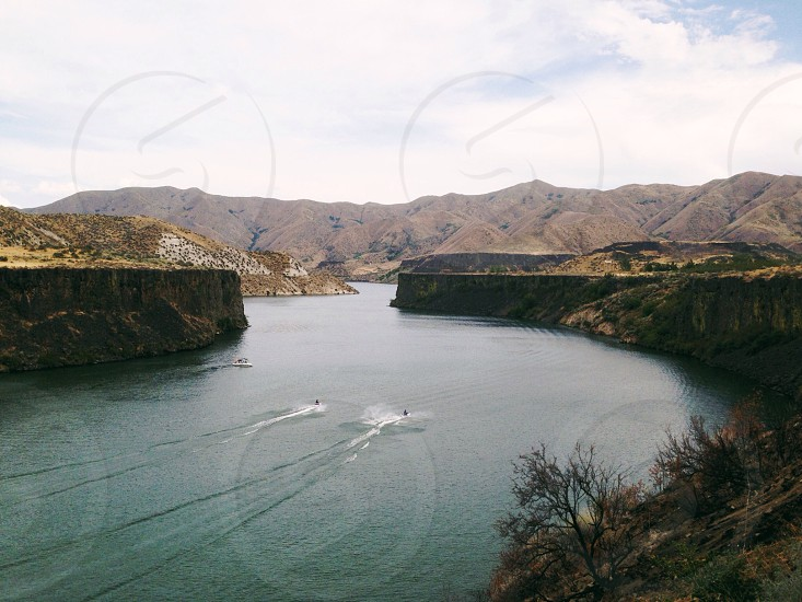Jet Skiers on a lake in Idaho surrounded by mountains and cliffs. photo