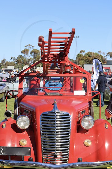 Vintage antique fire truck red retro history firefighting ladder hook and ladder engine grate chrome headlamps headlights outdoors Australia  photo