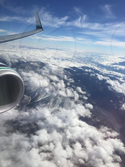 gray silver airplane wing over white clouds and black mountain ranges beneath blue white cloudy sky photo