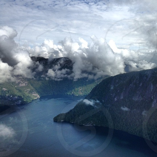 fog plane aerial point of view clouds mountains lake trees forest Alaska United States travel fog foggy dark cold winter contrast light private plane vacation.  photo