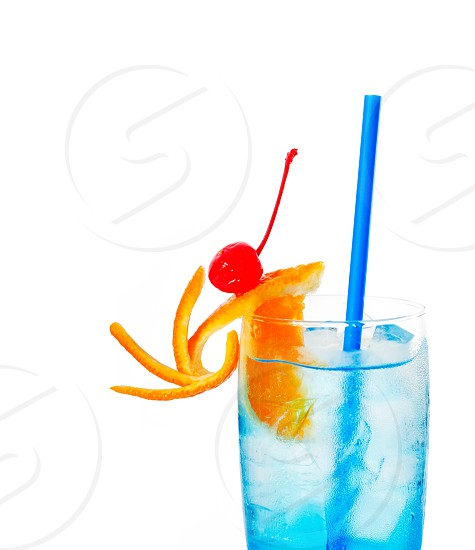 blue long drink cocktail with orange and cherry garnish and blue straw isolated on white background photo