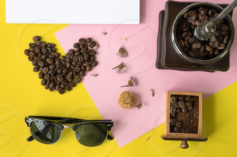 top view flat layer heart smile  icon shape sun glasses vintage wooden coffee grinder and blank book for copy space  on two tone multicoloured  background photo
