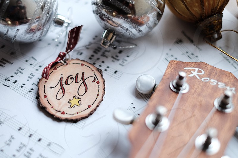 joy keychain on music sheet beside guitar and bauble photo