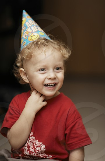 Cute happy young boy in a party hat laughing with enjoyment as he celebrates a birthday or Christmas photo
