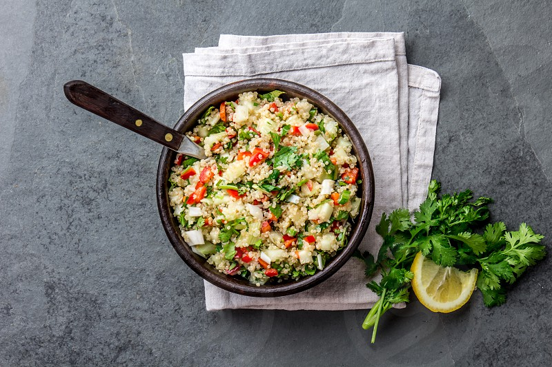 Traditional peruvian quinoa quinua salad in clay bowl slate gray background. photo