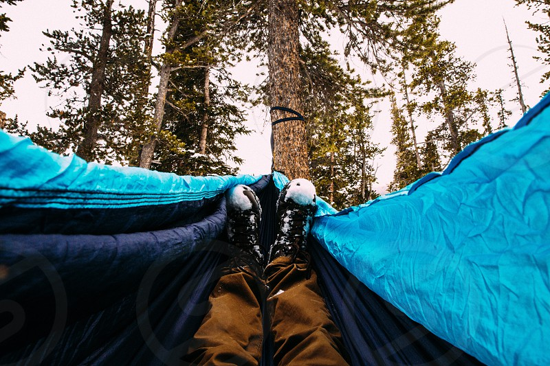 person lying on blue and black hammock during daytime photo