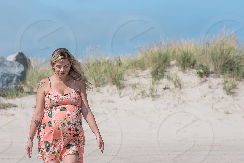 Picture of pregnant blonde white woman on the beach facing camera directly and smiling. photo