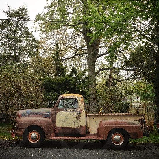 rusted vintage pickup truck parked on side of road photo