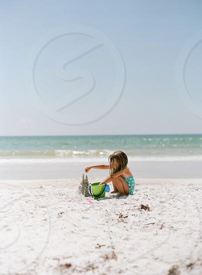 girl playing in sand photo