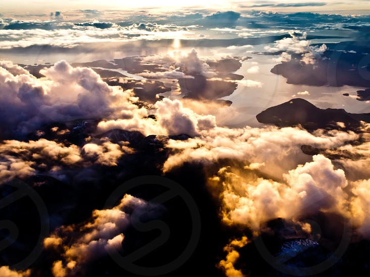 Aerial view of west coast mountains and fjords of British Columbia Canada with sun setting between tuffy clouds photo