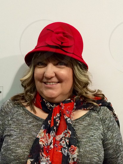woman smiling wearing red hat and gray sweater photo