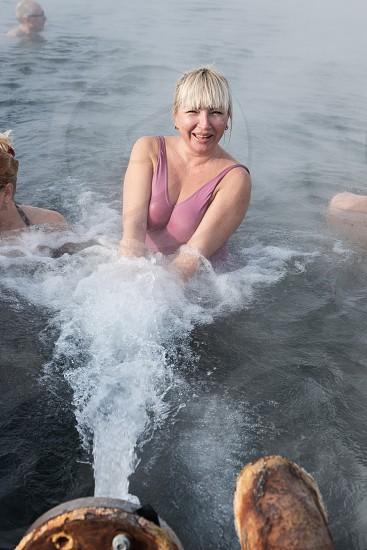 KAMCHATKA PENINSULA RUSSIA - FEB 02 2013: Satisfied woman relaxing in geothermal spa in hot spring pool in the winter. Eurasia Russian Far East Kamchatsky Krai Anavgay Village. photo