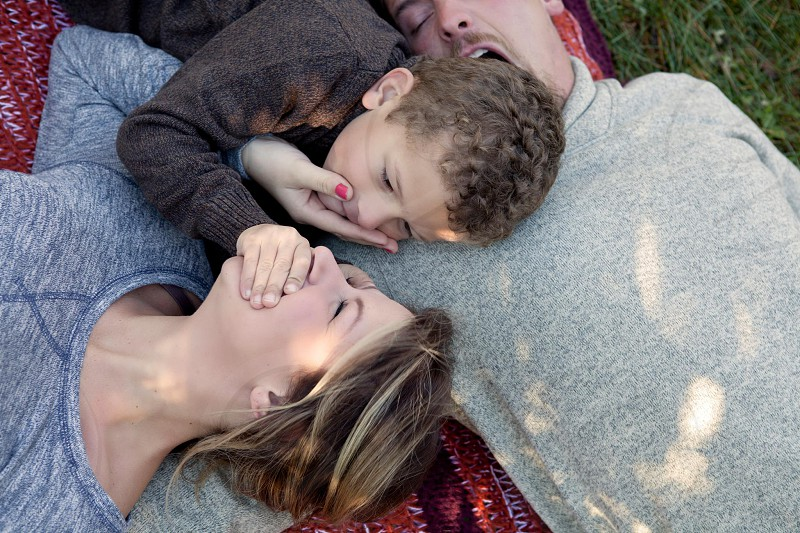 man woman and boy lying on red and orange picnic area rug photo