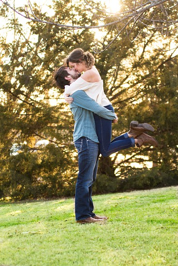 man standing on green grass kissing woman during sunset photo