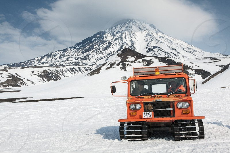 AVACHA PASS KAMCHATKA PENINSULA RUSSIA - APR 22 2012: Snowcat transportation for extreme sports sportsman (skiers and snowboarders) on the snowy slopes of the mountains. View snowcat with people on the background of the active Koryak Volcano. photo