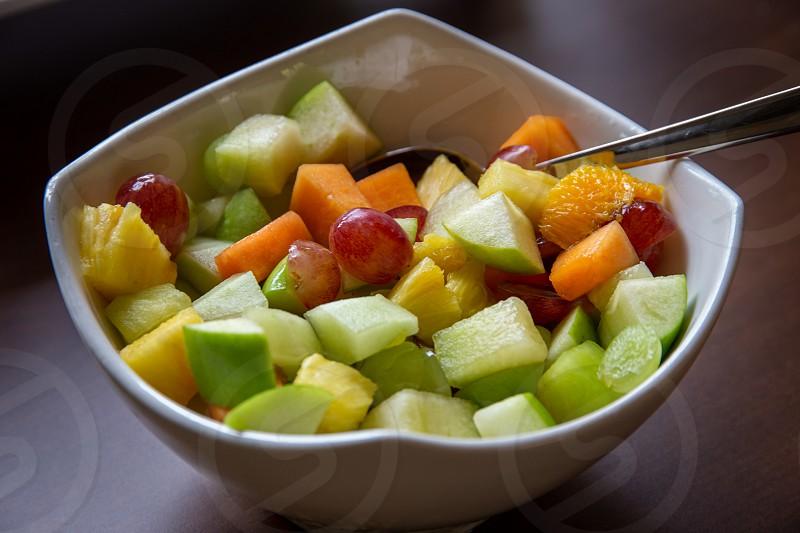 Large white bowl of healthy fresh fruit salad photo
