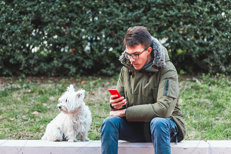 Young man sitting in the park with his dog using smartphone photo
