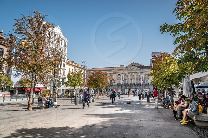 Scenic view of the Square of Saint Ann (Santa Ana) in Madrid a blue sky day. It is a plaza located in central Madrid in the Quarter of the Letters. It features monuments to writer Calderon and the poet Federico Garcia Lorca and numerous restaurants cafes and tapas bars with its terraces photo