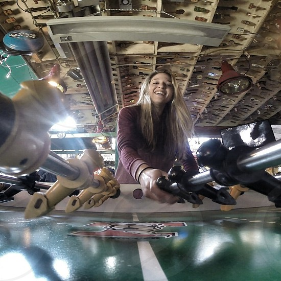 woman in pink long-sleeved shirt playing black white brown and green foosball table photo