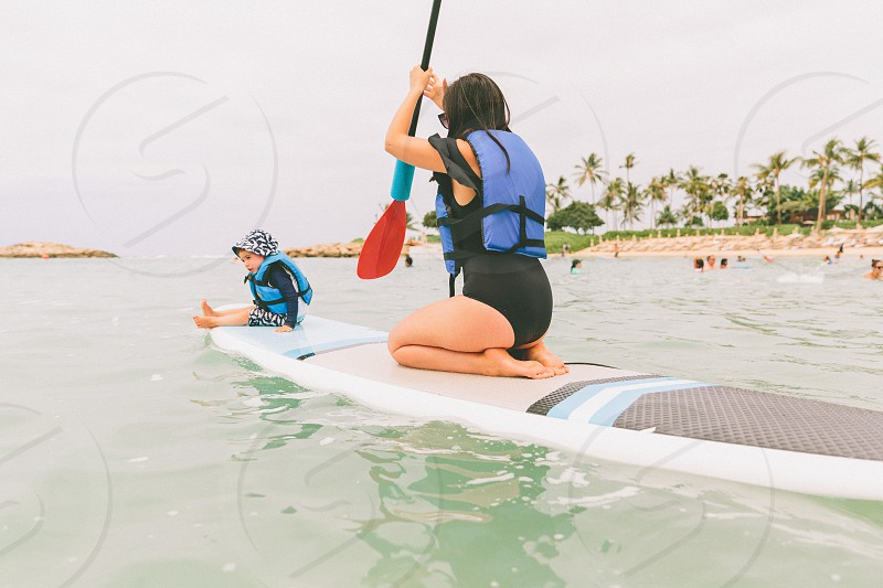 A mother paddle boarding with her son in Hawaii. photo