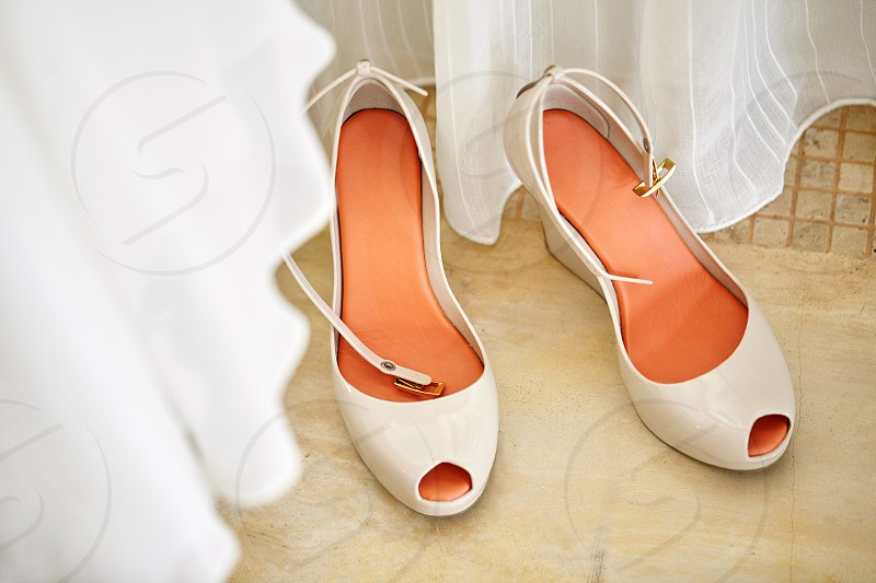 Beautiful women's nude pump shoes with orange-red insoles top-view with part of white cloth blurry in foreground photo