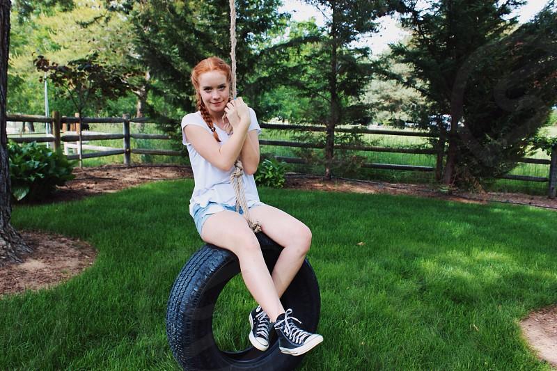 woman sitting on black tire swing at backyard photo