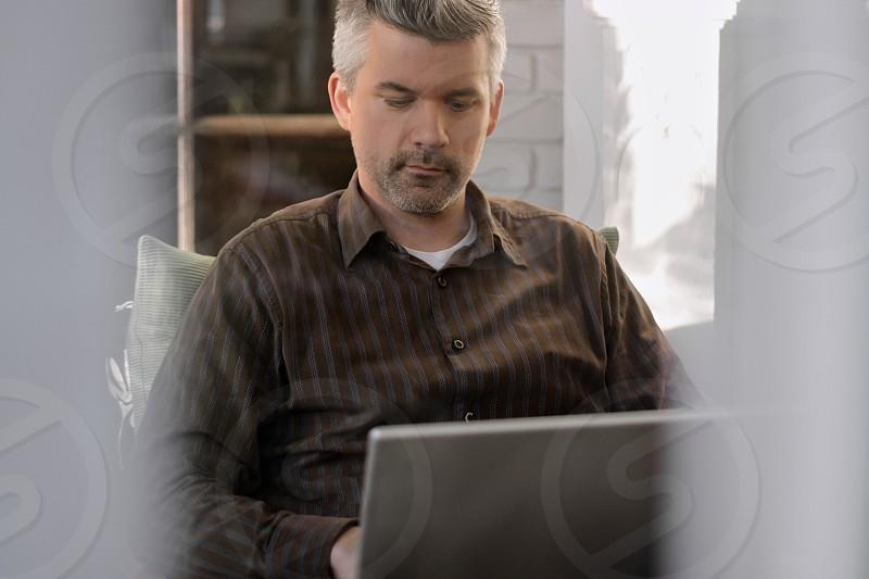 man in brown shirt using laptop  photo