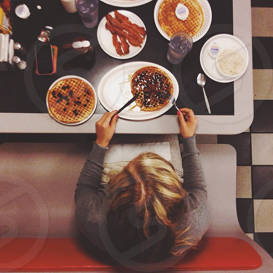 woman with brown long hair eating inside restaurant photo