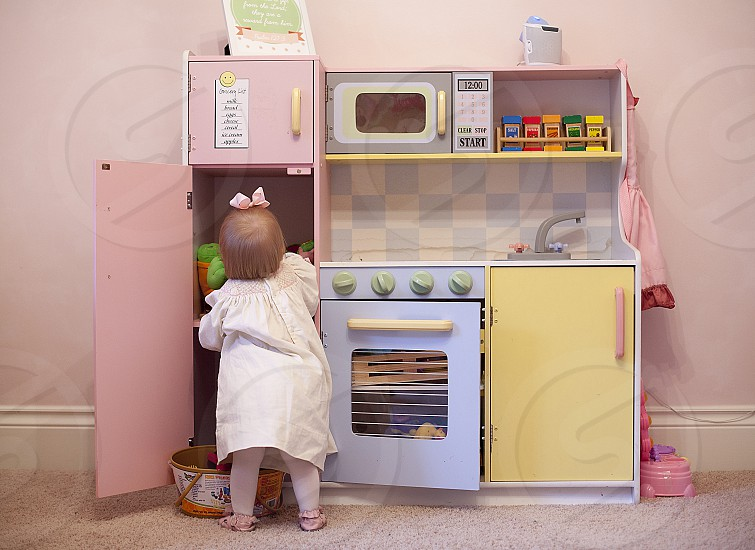 Baby sister playing with the kitchen in her bedroom photo