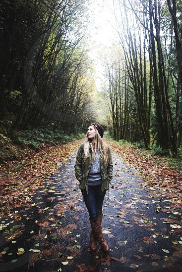 blonde woman in beanie on path between trees photo