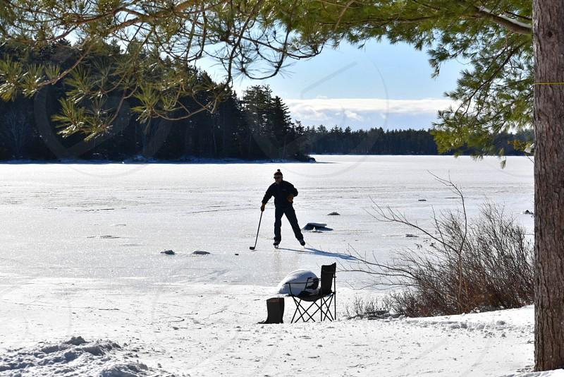 lake ice winter ice skating island snow hockey stick chair boots blue skies man hat Hirtle Lake Nova Scotia Canada evergreen trees winter activity landscape photo