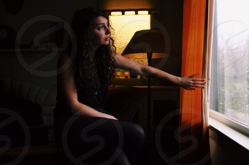 woman with long curly hair looking out of a rainy window photo