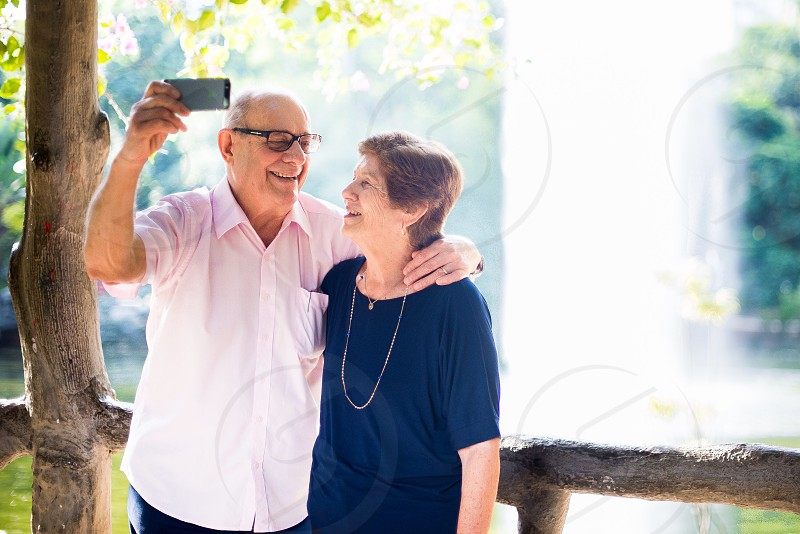 happy couple at the park taking pictures selfie senior  photo