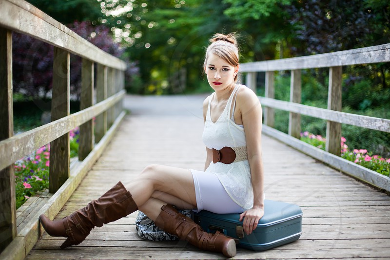Beautiful girl is sitting on luggage on a wooden bridge. Casual in a park during summer. photo