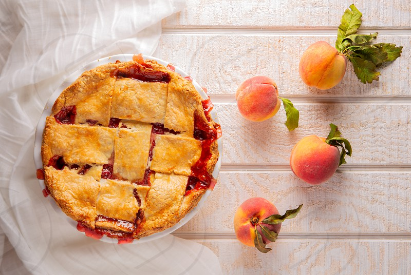 Peach pie with ripe peaches shot directly above on a white wooden surface photo