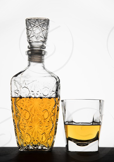 Whiskey in a glass and bottle enlightened from behind. photo