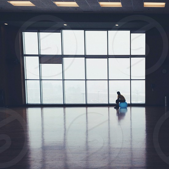 person sitting blue gym ball beside glass window photo