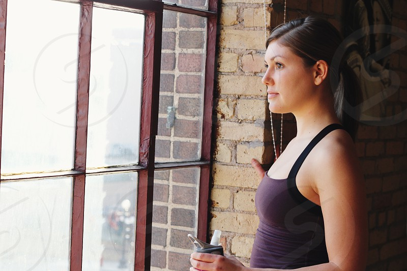 Woman looks out the window after yoga class with water bottle in hand. photo